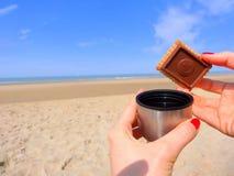 去野餐在海滩用茶和饼干 免版税库存图片