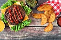 野餐场面用汉堡包和土豆楔住在黑暗的木头 免版税图库摄影