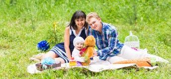 去野餐户外与他们逗人喜爱的女儿的家庭 库存图片