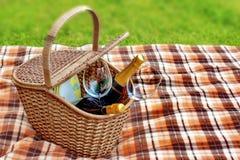 野餐毯子和篮子在草 免版税图库摄影
