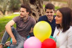 野餐的三青年人坐毯子在橄榄树下 免版税库存图片