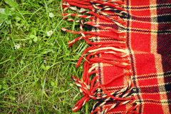 野餐的方格的格子花呢披肩在绿草 库存照片