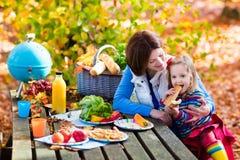 野餐的母亲和女儿集合桌在秋天 库存照片