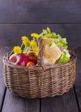 野餐的篮子用三明治、苹果、蕃茄和花 库存照片
