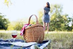 野餐篮子和妇女在背景中 免版税库存图片