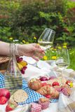 野餐篮子和食物 一个瓶酒和一块玻璃在妇女` s手上 romanica 有花的绿色草甸 在的春天 库存照片