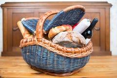 野餐篮子用新月形面包、面包、苹果、蒜味咸腊肠和酒 免版税库存照片