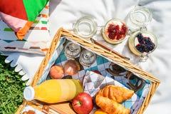 野餐篮子用果子,橙汁,新月形面包和没有烘烤蓝莓和草莓乳酪蛋糕 库存照片