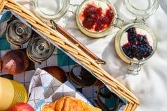 野餐篮子用果子,橙汁,新月形面包和没有烘烤蓝莓和草莓乳酪蛋糕 免版税库存图片