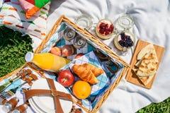 野餐篮子用果子,橙汁,新月形面包,油炸玉米粉饼和没有烘烤蓝莓和草莓乳酪蛋糕 图库摄影