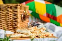野餐篮子用果子,橙汁,新月形面包,油炸玉米粉饼和没有烘烤蓝莓和草莓乳酪蛋糕 库存照片