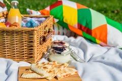 野餐篮子用果子,橙汁,新月形面包,油炸玉米粉饼和没有烘烤蓝莓和草莓乳酪蛋糕 免版税库存图片
