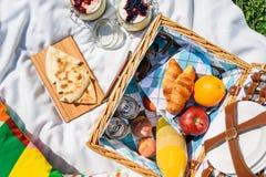 野餐篮子用果子,橙汁,新月形面包,油炸玉米粉饼和没有烘烤蓝莓和草莓乳酪蛋糕 免版税库存照片