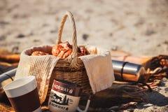 野餐篮子用面包、小圆面包、卷、热水瓶和杯子在海滩 户外野餐 库存图片