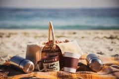 野餐篮子用面包、小圆面包、卷、热水瓶和杯子在海滩 户外野餐 免版税库存照片