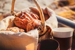 野餐篮子用面包、小圆面包、卷、热水瓶和杯子在 免版税图库摄影