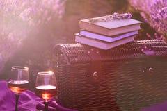 野餐篮子,旧书,玻璃喝酒在落日的光芒下 在日落的浪漫野餐概念在芬芳淡紫色 库存图片