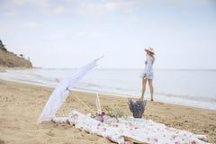 野餐,放松在一个狂放的海滩和漫步沿海滩的女孩的一个被弄脏的剪影在背景中 葡萄酒样式pho 免版税库存照片