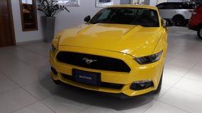 野马汽车黄色颜色在陈列室里 库存图片