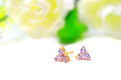 金下垂有浮雕的贝壳首饰和三颗金刚石宝石与花p 图库摄影