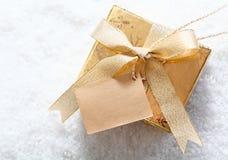 金与空白标签的礼物盒在雪 库存图片