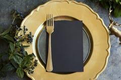 金与空的菜单的餐位餐具在难看的东西 免版税库存图片