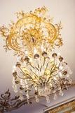 金与金装饰元素的枝形吊灯水晶在巴洛克式的样式的天花板 免版税库存图片
