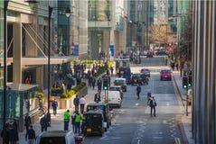 金丝雀码头与走的商人和运输lols的街道视图在路 事务和现代生活o 库存照片