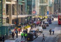金丝雀码头与走的商人和运输lols的街道视图在路 事务和现代生活o 图库摄影