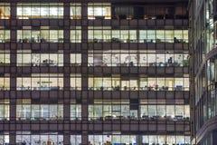 金丝雀码头办公室的窗口打开了在黄昏,企业生命力概念背景 免版税库存照片