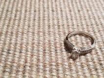 金刚石反对棕色织品背景的定婚戒指 库存照片