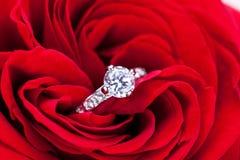 金刚石定婚戒指在一朵红色玫瑰的心脏 图库摄影