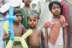 金刚石港口,印度- 3月30 :可怜的农村印地安孩子从传教士接受气球 库存照片