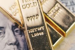 金制马上的齿龈、金块或者锭堆在美国美元钞票 库存图片