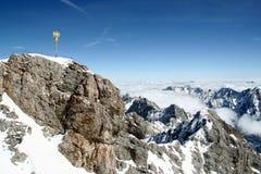 金十字架,在多雪的山峰,楚格峰山顶的立场  免版税库存图片