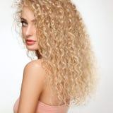 金发。有卷曲长的头发的美丽的妇女。 免版税库存照片