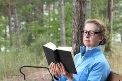 戴金发和眼镜的典雅的成熟妇女读一本书的外面在有拷贝空间的公园 免版税图库摄影