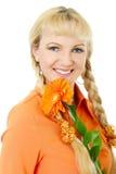 金发和蓝眼睛女孩橙色女衬衫的拿着花非洲雏菊 免版税库存照片