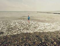 金发在冷的海浪潮的男孩逗留 在石海滩的孩子与泡沫似的波浪 有风的日 库存照片