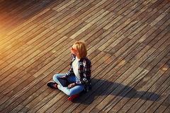 年轻金发学生坐看木的码头,火光太阳 免版税库存图片