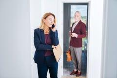 金发的不动产经纪人讲话由电话与她兴旺的客户 图库摄影