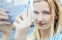 金发的女孩,拍在智能手机的照片,看behin 免版税库存图片