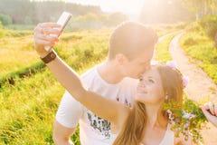 金发碧眼的女人做与她人亲吻的一selfie 图库摄影