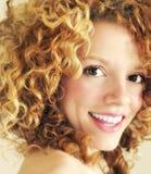 金发碧眼的女人卷曲愉快的微笑 库存照片