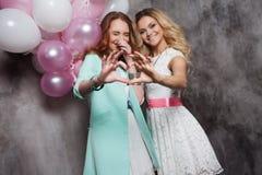 金发碧眼的女人和红头发人 党的两个年轻迷人的女朋友 显示标志心脏 在手上的焦点 免版税图库摄影