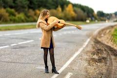 金发碧眼的女人在一件奶油色米黄外套和一件蓝色礼服,她的黑stocki采取了它喜欢小提琴的吉他和戏剧,夫人穿戴 免版税库存照片