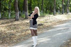 金发碧眼的女人在一条轨道花费在公园的美丽的妇女 免版税库存图片
