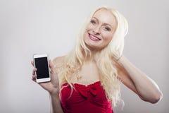 金发碧眼的女人在她的手上的拿着白细胞电话 免版税库存图片