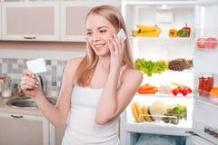 年轻金发碧眼的女人在家在冰箱附近 图库摄影