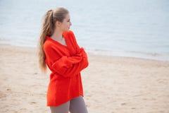 金发碧眼的女人在沙滩海岸周道地走 库存图片